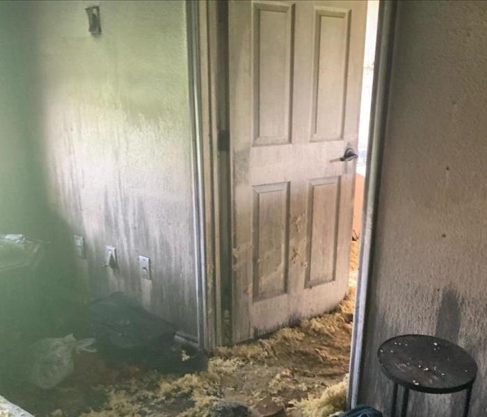This image depicts a home with heavy smoke damage as indicted by the amount of soot residue on the walls.