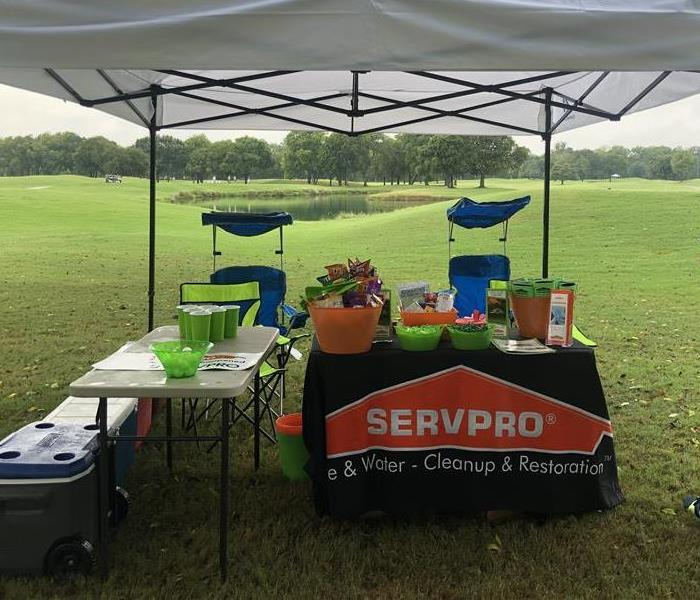 The Servpro table is set up on a golf course under a white tent with games and raffle items.