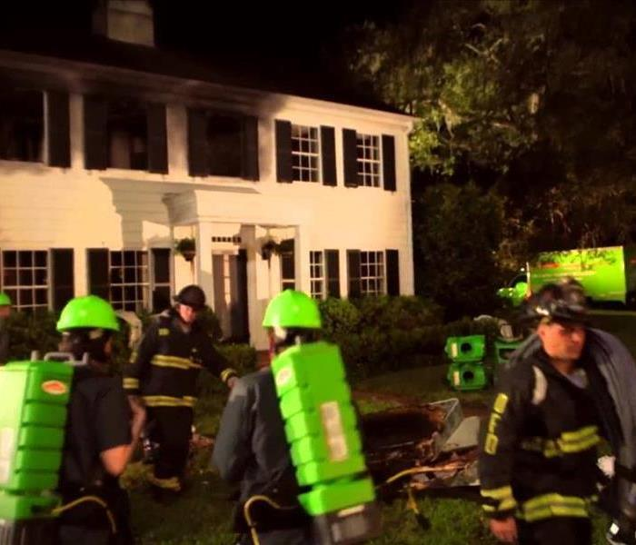 SERVPRO professionals and fire fighters outside a fire damaged home.